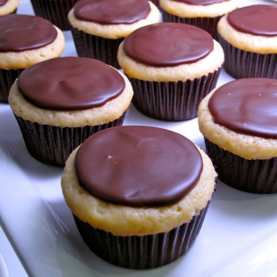 A vanilla cake, pastry cream filling topped with chocolate ganache cupcakes.