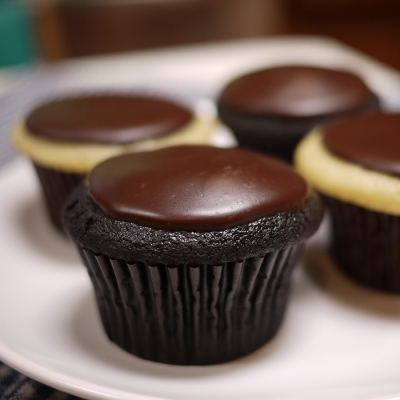 A photo vanilla cake, whipped cream filling topped with chocolate ganache cupcakes.