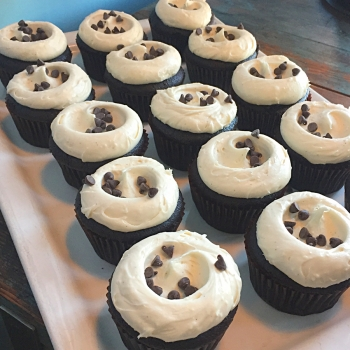A photo of chocolate cake with vanilla frosting cupcakes.